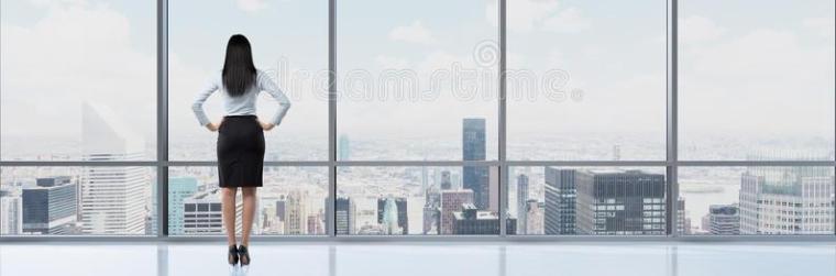 opinião-traseira-mulher-moreno-no-escritório-que-olha-através-da-janela-56233399